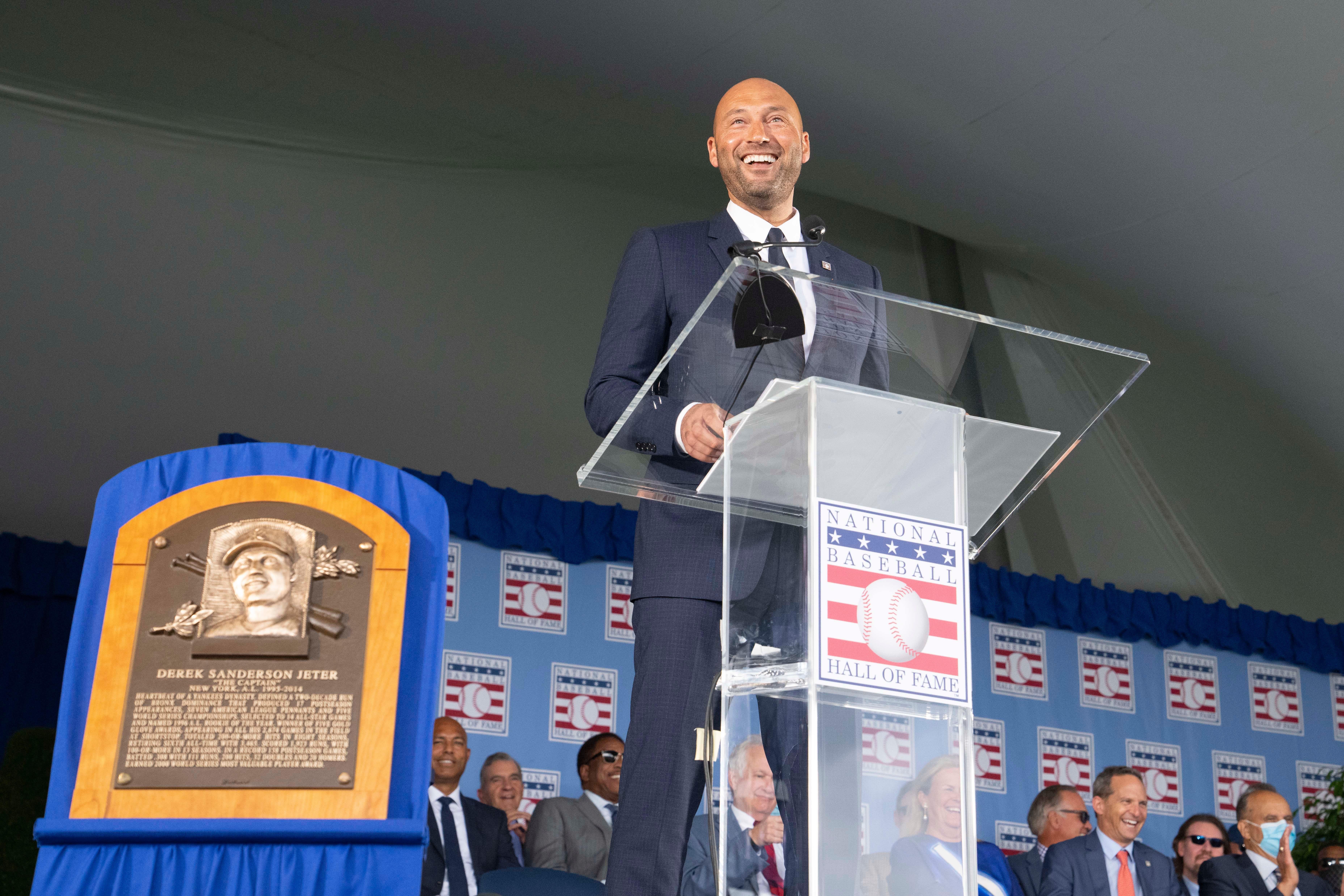 Derek Jeter smiles at a podium alongside his Baseball Hall of Fame plaque.
