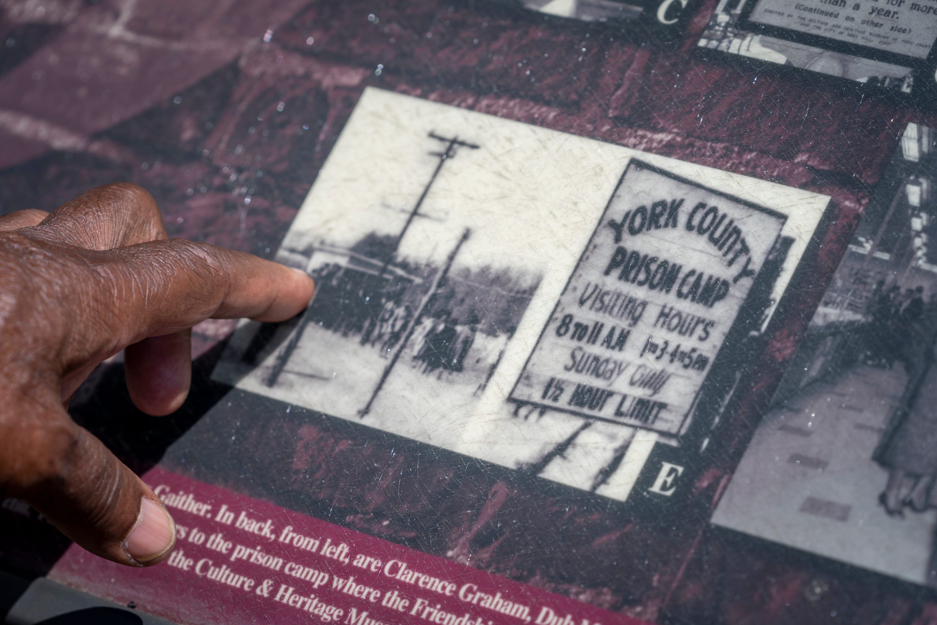 """David Williamson, one of the Friendship Nine, points to a photo of protest outside York County Prison Farm, where he was imprisoned for sitting in at McCrory's lunch counter, in Rock Hill, S.C. on August 12, 2021. On February 1, 1961,nine young civil rights activists were convicted of trespassing for staging a sit-in at a department store lunch counter in Rock Hill, South Carolina. The judge imposed a fine of $100 each or 30 days hard labor on a chain gang. The activists opted for jail time, setting in motion the movement's """"Jail-No-Bail'' strategy to push back against paying fines for fighting segregation. Experts said the strategy became a key tactic in the civil rights movement, including one used by the Freedom Riders. It also draws some parallels to the debate today over the disparate impact of the bail system on people of color, experts and veteran said."""
