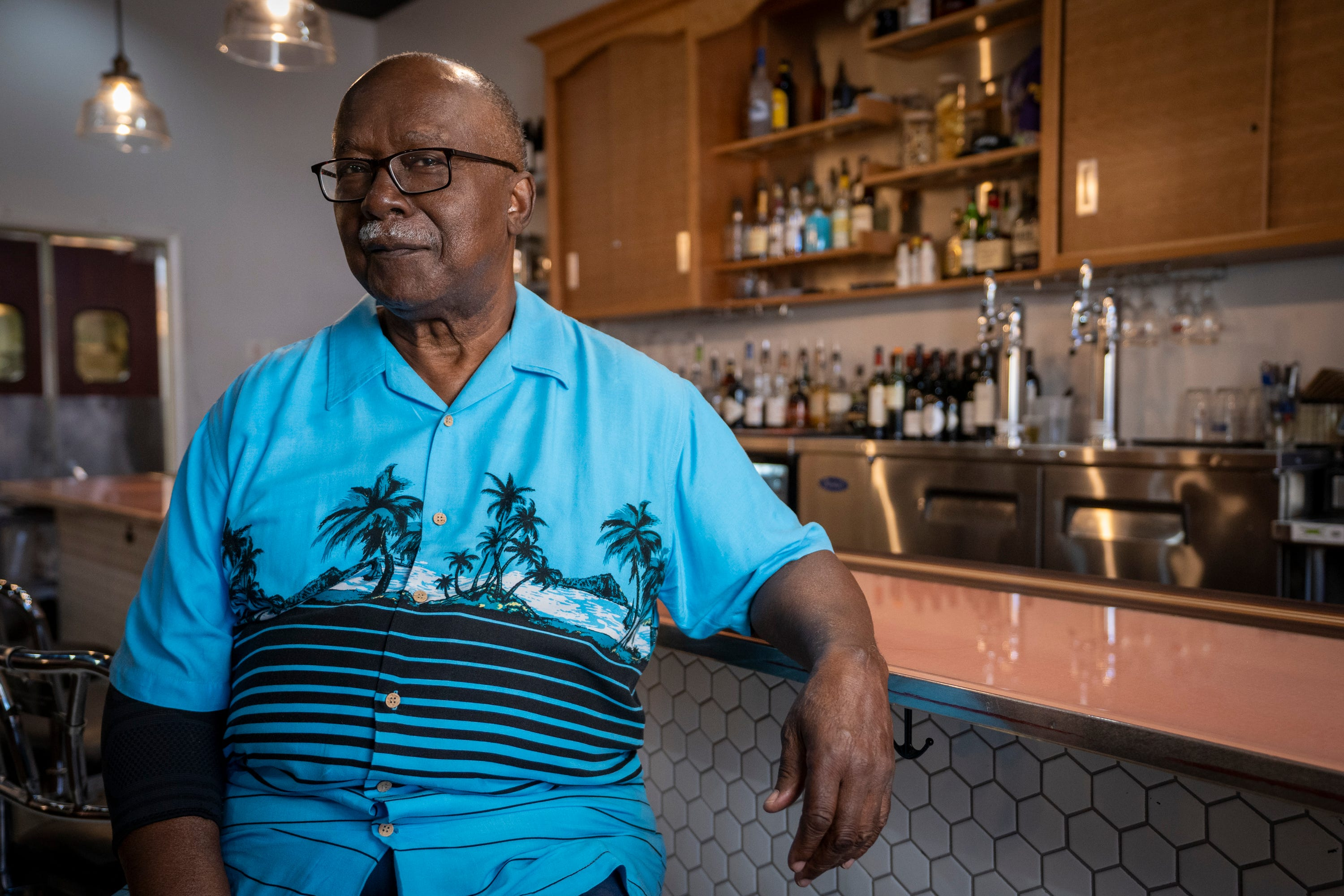 """David Williamson sits for a portrait at the original McCrory's Five and Dime lunch counter, restored and preserved by the owners of Kounter, in Rock Hill, S.C., on Aug. 12, 2021. On Feb. 1, 1961, 10 young civil rights activists were convicted of trespassing for staging a sit-in at a department store lunch counter in Rock Hill, South Carolina. The judge imposed a fine of $100 each or 30 days hard labor on a chain gang. Nine of the activists opted for jail time, setting in motion the movement's """"jail, no bail'' strategy to push back against paying fines for fighting segregation."""