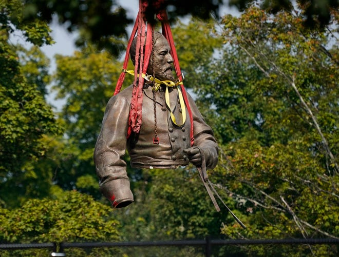 A section of the statue of Confederate Gen. Robert E. Lee in Richmond, Va., is suspended by straps as it is moved to a truck for removal on Wednesday, Sept. 8, 2021.