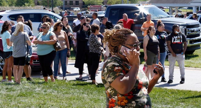 Parents wait around Lake Central High School to hear information about their children during a lock down for a report of an active shooter incident Wednesday, Sept. 8, 2021 in St. John, Ind.