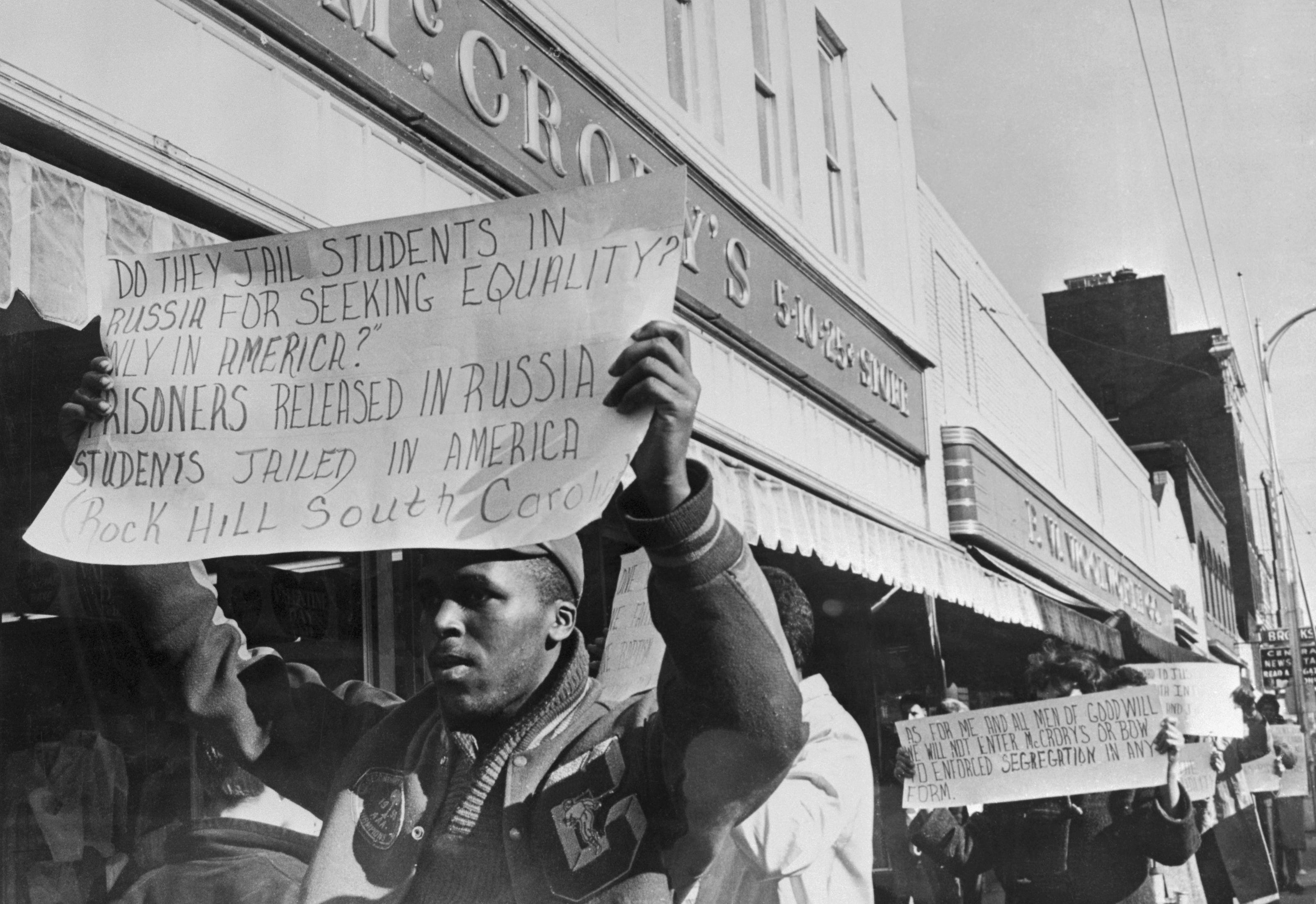 """A student carrying a sign walks past McCrory's Five & Dime during a protest over segregated eating places. The sign read, """"Do they jail students in Russia for seeking equality? Or only in America? Prisoners released in Russia, students jailed in America."""""""