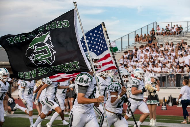 Cedar Park kicker Ralan Barr, left, and running back Tyree Nicholson lead their team onto the field before a nondistrict football game at Vandegrift High School on Aug. 27. From the first week of this season through Wednesday, four games in the Austin area have been canceled because of COVID-19 issues with local schools compared to almost 100 across the state.
