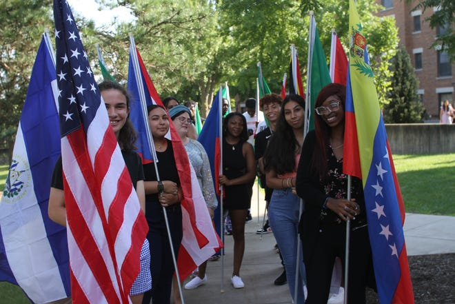 Keuka College students, holding flags from their native counties, prepare to lead the student processional into Norton Chapel for the College's annual Academic Convocation.
