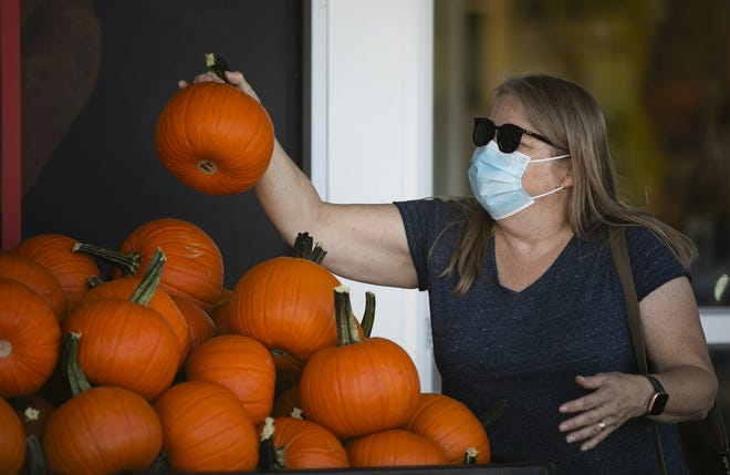 Pam Downing wears a face mask as she picks out pumpkins Sept. 9 at Lucky's Market in Clintonville.  Mayor Andrew Ginther on Tuesday signed a beefed up mask mandate law on Tuesday adopted the night before by City Council.  The measure increases fines for businesses and individuals, but also offers lots of exemptions.