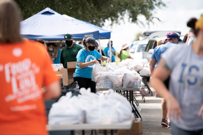 Volunteers load cars full of groceries at a Second Harvest food drop in 2020.