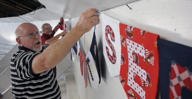 Frank Meshew and Jeff Fickes hang the letters in their quilts for the veterans booth in the rotunda at the Wayne County Fairgrounds in preparation for the Wayne County Fair.