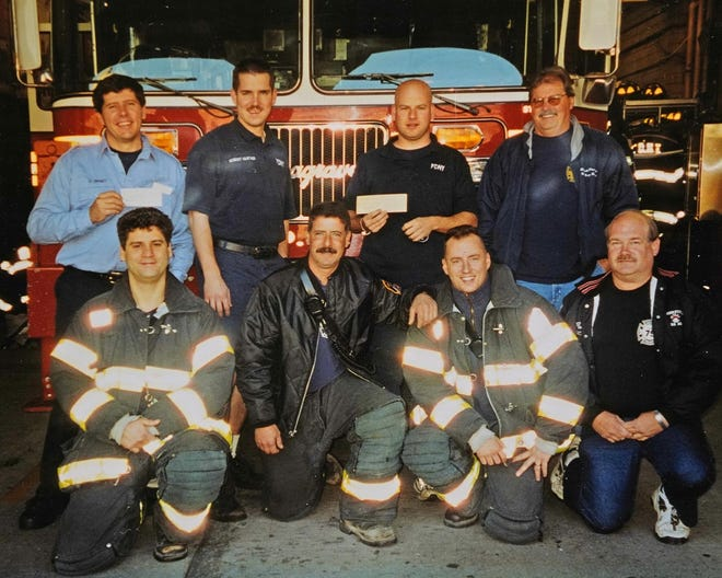 Ron Cousino and Gary Lombard, are pictured at the fire department in New York City's Hell's Kitchen after delivering a $5,000 check to be split among six families whose loved ones perished when the twin towers collapsed. Cousino is far right front, and Lombard is far right back row.