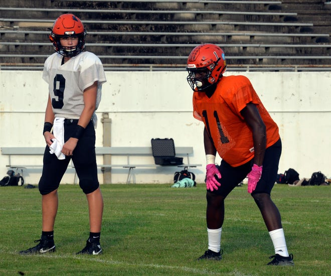 North Davidson quarterback Gavin Hill looks for the call before running a play in a scrimmage last month in High Point. At right is tailback Xavion Hayes. [Mike Duprez/The Dispatch]