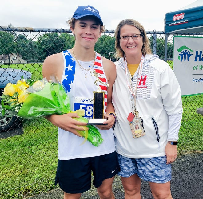 """Honesdale distance running star Aidan LaTourette finished first overall at Habitat for Humanity's 25th annual """"Run for the Roses."""" Aidan is pictured here with Diane Scarfalloto who presented him with his roses and trophy."""