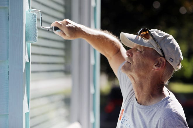 Jay Clover, a volunteer from First Church of the Nazarene, paints Laurie Powell's home Wednesday during the Burlington/West Burlington Paint-A-Thon in Burlington. The home, which originally was a dark barn red color, was painted two years ago, but the old color was showing on parts of the home so volunteers returned this year to touch up and repaint the house. Volunteers fanned out over Burlington and West Burlington this week to paint homes in the annual Paint-A-Thon, helping those who don't have the resources or money to do it themselves.