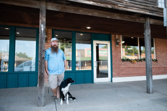 Chris Foster, the owner of F6 Ranchwear, stands outside his new storefront with his cattle dog Zip. F6 Ranchwear opened its storefront in late July and has found success with the Buhler community and beyond.