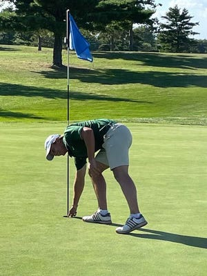 Richwoods senior Jack Hammerton gets his ball out of the sixth hole following a hole-in-one.