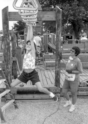 In this Journal Star file photo from May 17, 1992, Lisa Kellogg, 10, crosses the ring bridge while her mother, Lois, looks on at the Tricentennial Playground in Glen Oak Park. Lois Kellogg was among more than 350 volunteers who put the finishing touches on the 12,000-square-foot recreation area.