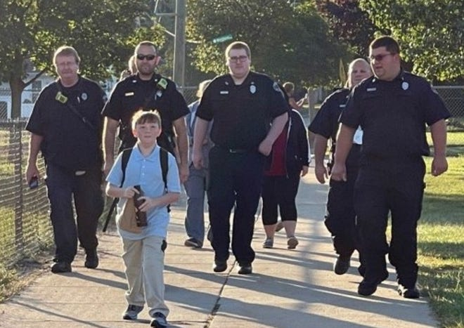 Monroe Charter Township Fire Department firefighters walk Tony Brown, a fifth-grader at Waterloo Elementary School, to his first day of school. Tony's father, Frank Brown, who was a firefighter with the department, died in a boating accident in August.