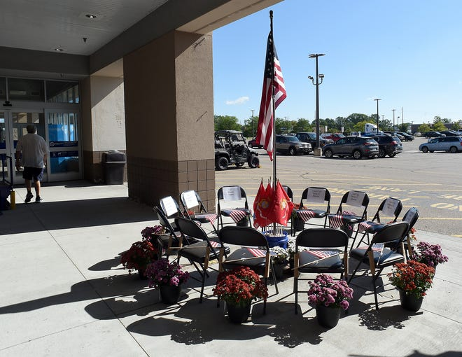 Thirteen chairs, flags of the armed forces and mums are displayed outside Lowe's on Telegraph to honor the 13 serviceman killed in Afghanistan. Eleven Marines, one Navy sailor and an Army soldier lost their lives in Kabul when a suicide bomber detonated explosives at the airport gate where U.S. troops were assisting evacuees rushing to depart the country on August 26. The names and rank of the fallen are taped to each chair. Also, an American flag rests on each seat.