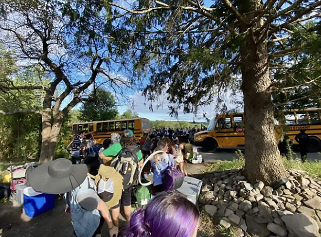 Attendees at the Elements Music and Arts Festival in Wayne County await shuttle rides to Camp Lavi, where the event was hosted. Guests have flooded social media platforms since the festival describing muddy, cramped camping spaces, a lack of water and food, and more issues.