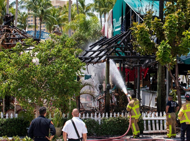 Firefighters hose down the remains of some tiki huts after a fire that also damaged the awning of ER Bradley's in downtown West Palm Beach, Thursday afternoon, Sept. 9, 2021. Flames were visible as firefighters arrived. Damage was confined to the exterior. No one was in the building at the time, which was tented for pest control, and there were no injuries.