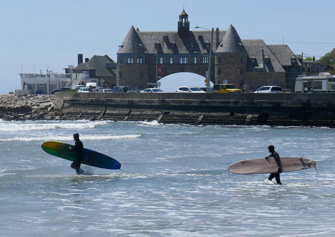 Surfers head out from Narragansett Town Beach in search of waves.