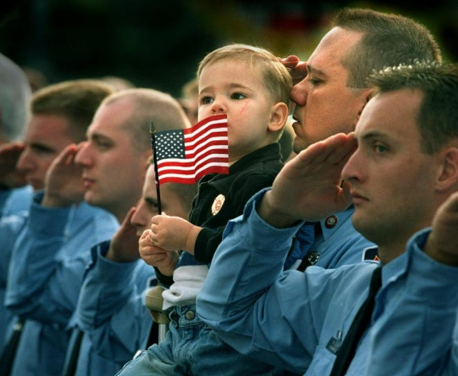 A 2-year-old son watches a firefighter memorial from the arms of his firefighter father during a ceremony at the Eugene Public Safety Center in Eugene. About 150 uniformed officers were in attendance at the Sept. 14, 2001, ceremony.