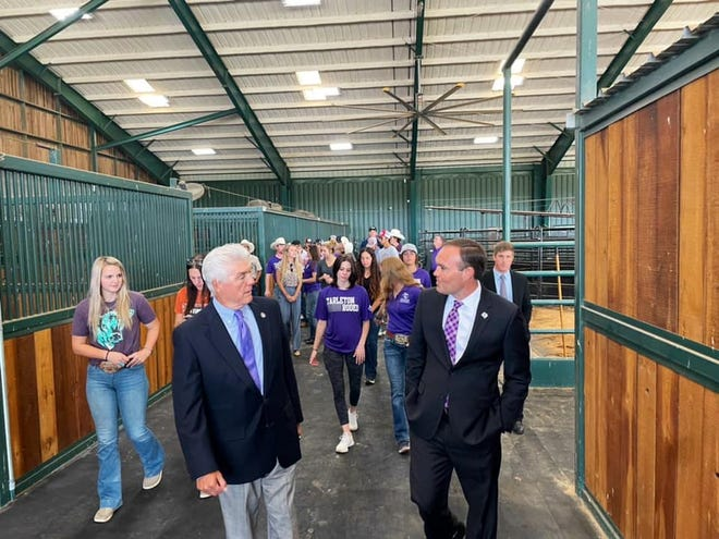 Rep. Roger Williams, R-Texas 25, left, walks with Tarleton State University President James Hurley and members of the Tarleton Rodeo Team during a Thursday morning visit to TSU's rodeo facilities.