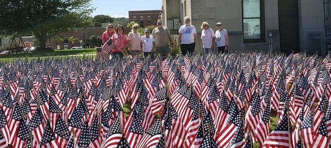Volunteers gathered after getting the first grid of 750 flags placed on the lawn of the Owen County Courthouse. On Wednesday, 2996 flags were placed on the lawn to represent the lives lost on 9-11-01. On Saturday, 9-11-21, the 'We Remember' event will take place to honor those lives lost as well to honor the life and service of Owen County's own PFC Brett Wood, who tragically lost his life on 9-9-11. Along with the flag display, the vent will feature the playing of Taps, a presentation of the flag to Brett's brother Nikk Wood, a 21-gun salute and special guests. The event begins at 11 a.m. and lunch will follow. Sponsors and supporters of the event include, the Owen County Sheriff's Department, Vincennes VFW Post 1157, American Legion Post 285, Gosport VFW Post 7850, Owen County Commissioners, Owen County Community Foundation, Owen County Chamber of Commerce and VFW Auxiliary Post 1405.