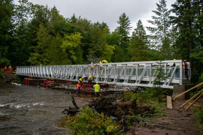 Workmen on the new pedestrian bridge at the Lower Tahquamenon Falls after all four segments have been lifted into place.