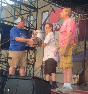 """David Guzzardo was finally given his due Sunday night on the main stage during the Kewanee Hog Days Festival. Guzzardo received a gift basket from Committee member, Mike Komnick, left,  and Co-Chair Larry Flannery, right, for choosing the Hog Days 2020 theme, """"If You Have It, They Will Come."""" Just like the festival in 2020, the presentation of the Guzzardo's prize was postponed."""