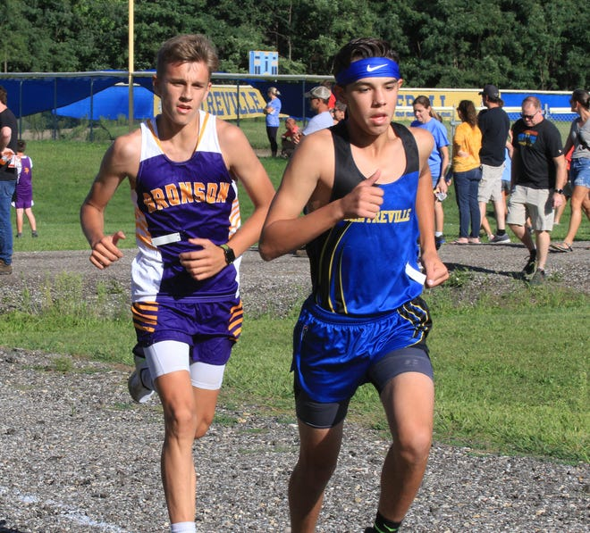 Bronson's Aden Hathaway runs with Centreville's Logan Weis during cross country action on Wednesday.
