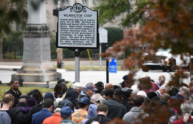 People stand under a North Carolina highway historical marker to the 1898 Wilmington Coup shortly after it was unveiled during a dedication ceremony in downtown Wilmington, N.C., Friday, November 8, 2019. The marker stands outside the Wilmington Light Infantry building, the location where a mob of white supremacists originally gathered.