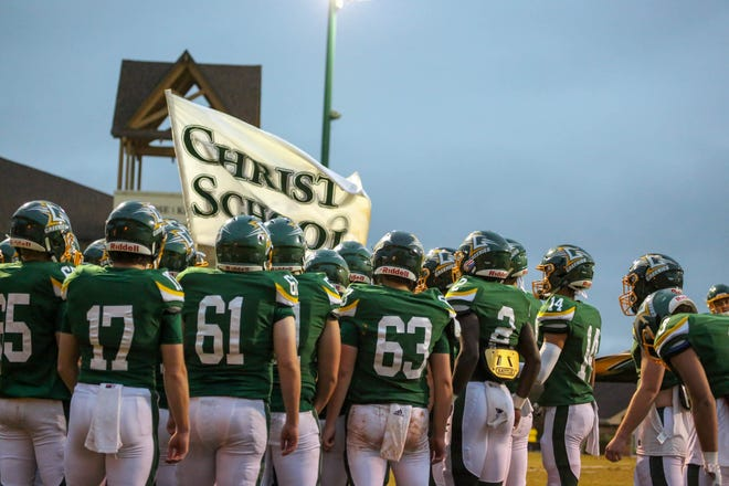 The Christ School football team huddles before a home game against rival Asheville School on Oct. 31, 2020. With eight Division I commits among their 2020 and 2021 graduating classes, the reigning NCISAA Division II state champion Greenies are on a serious recruiting hot streak that should only continue in future classes.