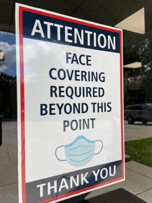 A sign on the front door of the North Lawrence Community Schools Administration Building informs anyone entering that they must wear a face covering.