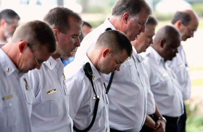 Tuscaloosa Fire Rescue firefighters Joe Fair, left, Steve Zark, Steve Cornett and now-retired Battalion Chief Eddie Pugh, fourth from right, are pictured in this 2009 file photo reflecting during a moment of silence at Station 1. That year, fire departments across the nation observed a moment of silence at 7:46 a.m. CST, the hour and minute American Airlines Flight 11 struck the north tower of the World Trade Center in 2001.