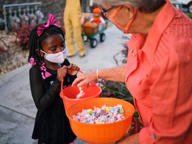 Children trick or treating on Halloween wearing facemarks for protection.