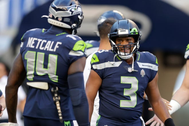 Seahawks quarterback Russell Wilson greets DK Metcalf (14) during warmups before the preseason game against the Chargers. With Wilson back Seattle has top-line talent to make a deep playoff run, but a lack of depth could make a pivotal season more risky.