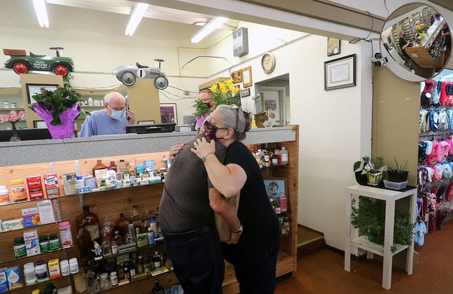 Pharmacy tech Laura Niemann hugs long-time customer Ernie Hahn as pharmacist Ken Paskett answers the phone behind the counter during the last day of pharmacy service at South Park Pharmacy in Port Orchard on Thursday. After 53 years of service, the neighborhood pharmacy is closing its doors.
