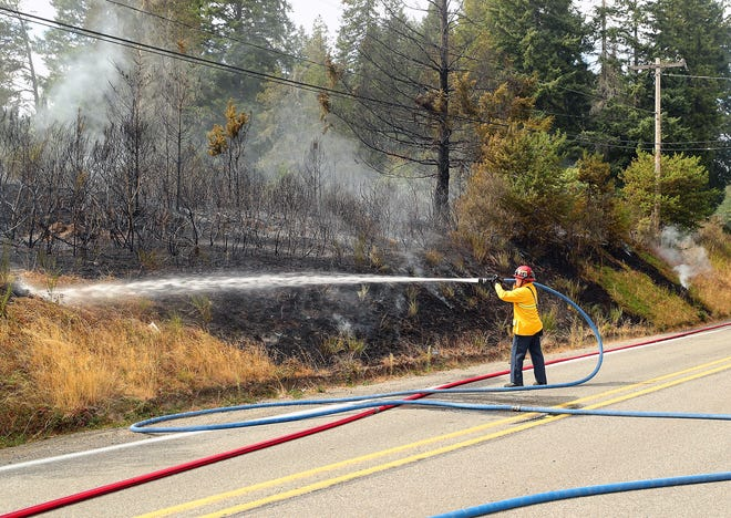 A Navy Region Northwest firefighter sprays down the smoking vegetation along Seabeck Highway as Navy and CKFR crews put out a two-alarm vegetation fire at Camp Wesley Harris on Thursday.