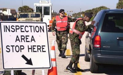 A Florida National Guard soldier checks the back of a minivan on State Road A1A at the south end of Patrick Air Force Base in January 2002. The road was closed in front of the base for months following the 9/11 attacks.