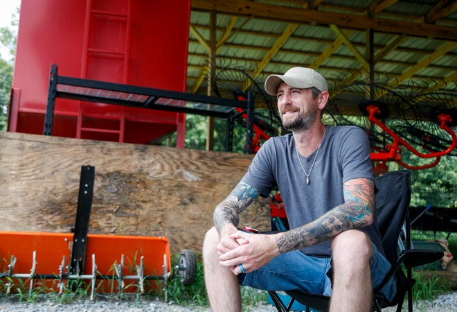 Brandon French sits in a camp chair underneath one of the shelters on his land at the French family farm in Clarksville, Tenn., on Saturday, July 31, 2021.