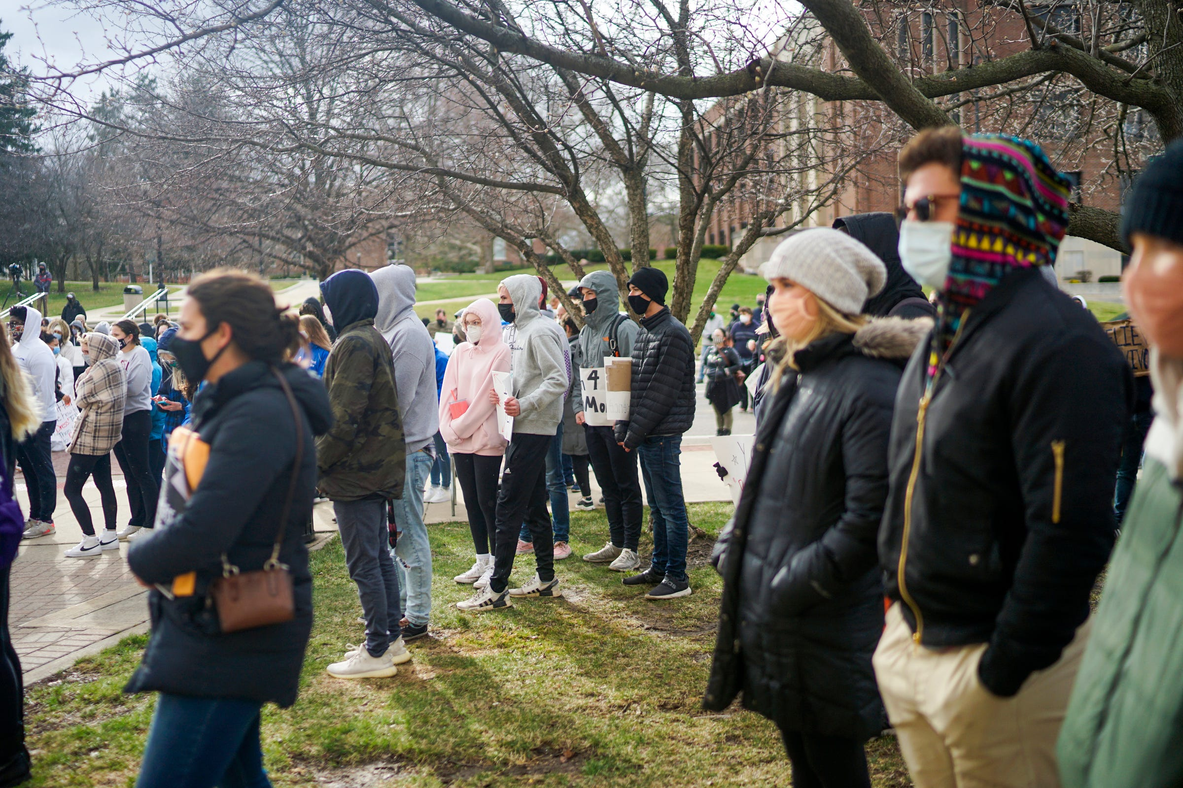 People listen to speakers during a protest at Eastern Michigan University on Sunday, March 28, 2021, in Ypsilanti supporting sexual assault survivors in response to news of 11 women who filed a lawsuit against EMU. The Title IX lawsuit was filed the prior week against the Eastern Michigan University Board of Regents and two fraternities, saying they covered up and failed to adequately address sexual assaults by several male students, according to previous Free Press reporting.