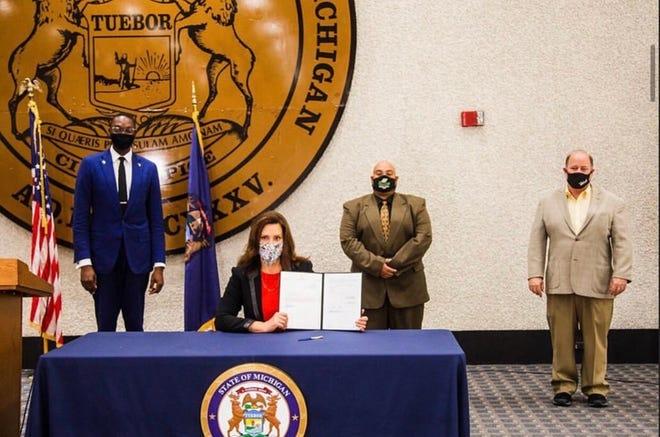 La gobernadora Gretchen Whitmer posa con el proyecto de ley de justicia penal limpio firmado con el vicegobernador Garlin Gilchrist (izquierda), Héctor Santiago (centro) y el alcalde Mike Duggan el 12 de octubre de 2020 en Lansing, Michigan.
