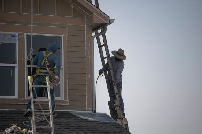 Construction workers work on a residential unit in the Timnath Lakes community, Wednesday, Sept. 8, 2021.