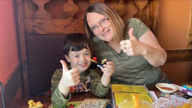 Tammy Murphy holds her thumbs up while sitting with her grandson Kenny. Murphy was a bus driver for Knox County Schools and died after battling COVID-19.