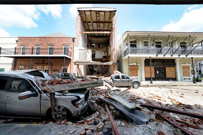 A structurally compromised building in downtown Thibodaux  was further destroyed by Hurricane Ida and trashed vehicles below that were located nearby. Onlookers stopped on Sept. 7, 2021, to observe the damage.