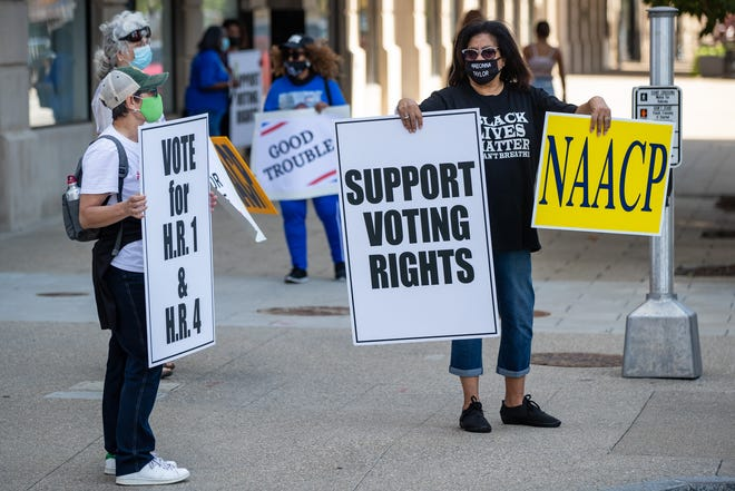 D.M. Honeycutt, left, and Dr. Annette Bridges hold signs with others in support of the voting rights legislation H.R. 1 and H.R. 4.