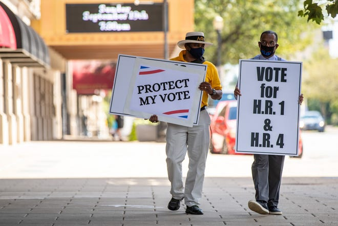Protesters in support of the voting rights legislation H.R. 1 and H.R. 4 hold signs outside the Brown Hotel where Sen. Mitch McConnell delivered a speech Thursday. Sen. McConnell has opposed the voting rights legislation. Sept. 9, 2021
