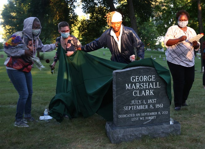 Tyrone Randle, (second from right) who lead the efforts to raise funds for the unmarked grave of George Marshall Clark, is helped with the unveiling with Kamila Ahmed, left and Aadya (cq) Wyhtner Forest Home Cemetery in Milwaukee. Clark is the only recorded lynching in Milwaukee that took place on Sept. 8, 1861 at the corner of Water and Buffalo streets in Milwaukee.