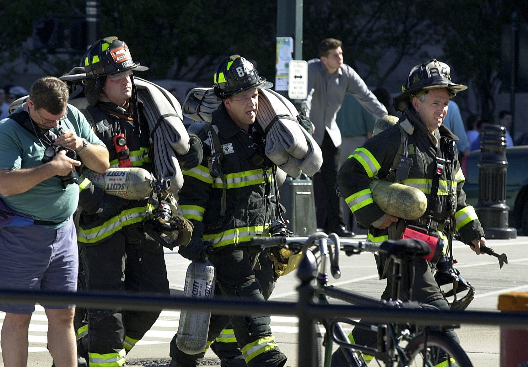 Veteran New York firefighters make their way along the West Side Highway toward the north tower of the World Trade on Sept. 11, 2001. Many of their younger peers were already in the twin towers trying to rescue trapped workers.  The south tower collapsed 12 minutes later.