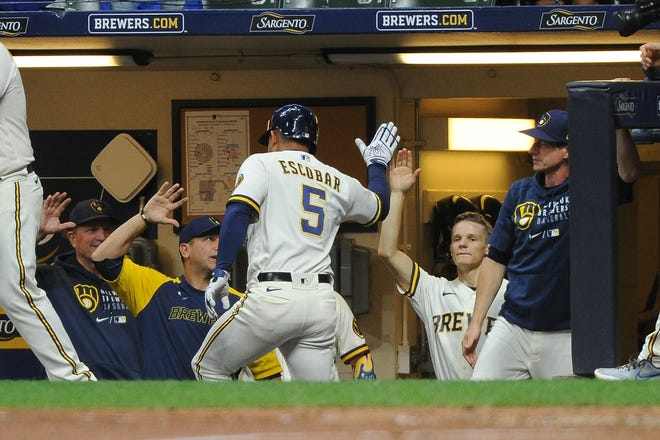 Eduardo Escobar is greeted by teammates and coaches in the Brewers dugout after hitting a go-ahead solo home run against the Phillies in the sixth inning Wednesday night.