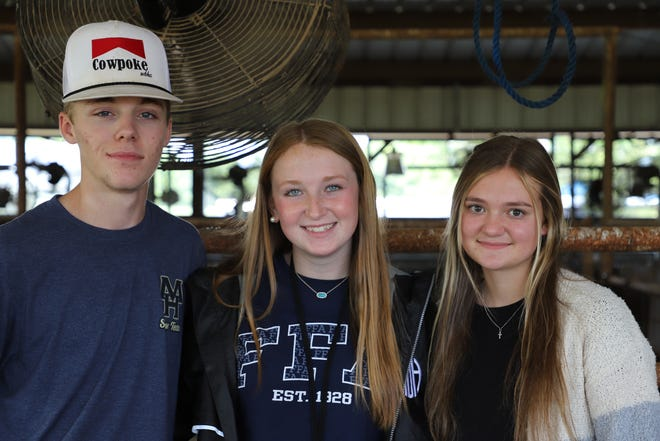 Colton Cooley (left), Madison Hutson (center) and Kelsey Roach pose for a photo outside the animal pens at Mountain Home High School. FFA students are responsible for maintaining the pens and the livestock on campus.